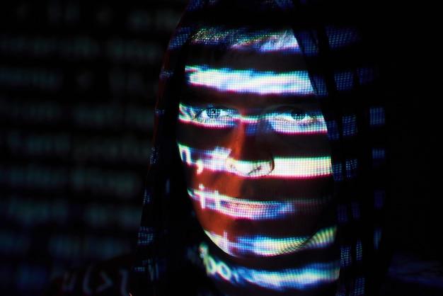 Cyberatak z nierozpoznawalnym hakerem z kapturem wykorzystującym wirtualną rzeczywistość, cyfrowy efekt usterki