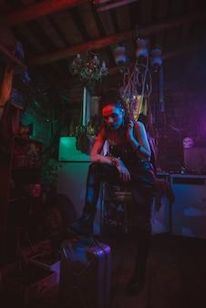 Cyberpunkowa dziewczyna w postapokaliptycznym futurystycznym stylu w garażu z neonowym światłem. steampunkowy cosplay