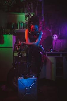 Cyberpunkowy cosplay. dziewczyna w masce gazowej w postapokaliptycznym stylu z neonowym oświetleniem. kostium i makijaż steampunk