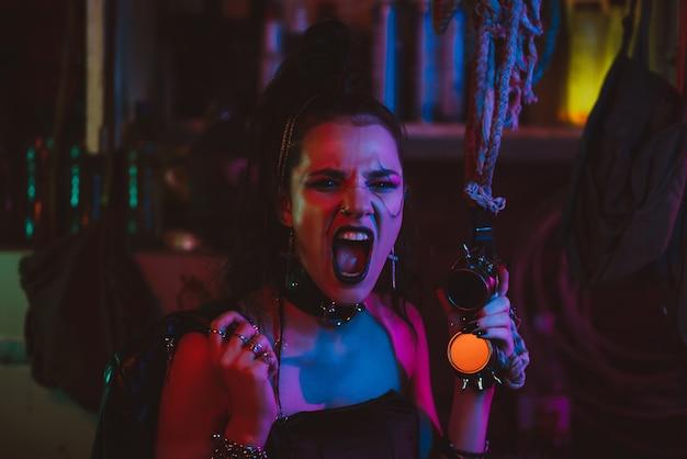 Cyberpunkowy cosplay. dziewczyna z makijażem i stylizacją włosów w futurystycznym stylu steampunkowym z neonowym oświetleniem. postapokaliptyczny styl