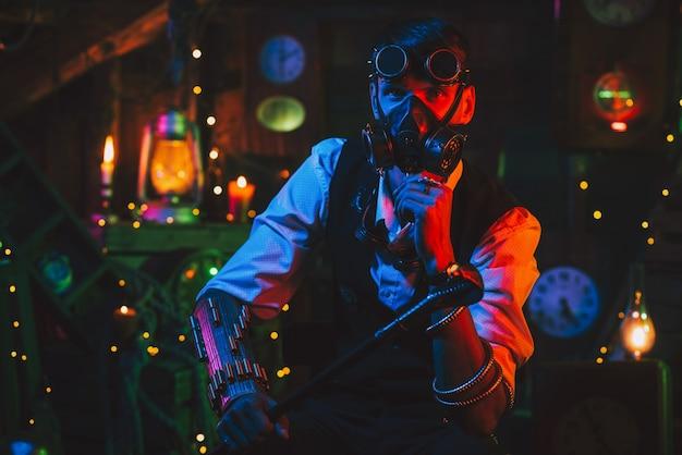 Cyberpunkowy postapokaliptyczny cosplay. inżynier w okularach i masce gazowej w warsztacie z neonowym światłem