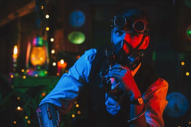 Cyberpunkowy postapokaliptyczny cosplay. mężczyzna w okularach i masce gazowej w warsztacie z neonowym światłem