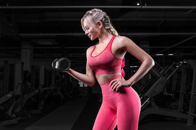 Cycata blondynka w różowym dresie z hantlami pozuje na siłowni. koncepcja fitness.