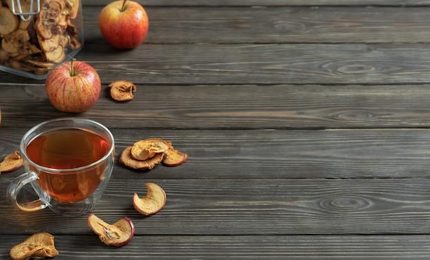 Cydr jabłkowy w szklanym kubku ze słomką i suszonymi jabłkami z dojrzałymi jabłkami