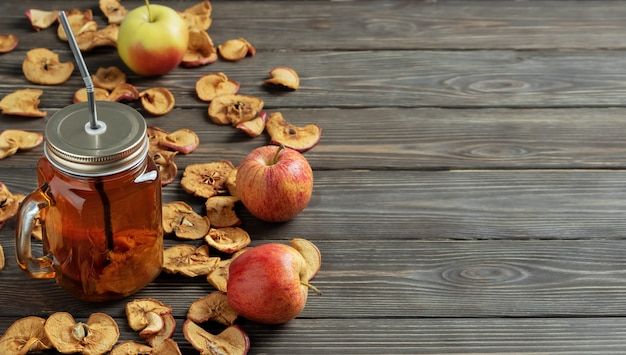 Cydr jabłkowy w szklanym słoju ze słomką i suszonymi jabłkami z dojrzałymi jabłkami