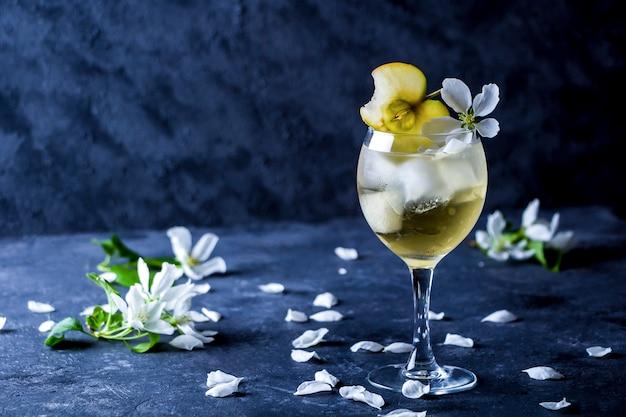 Cydr jabłkowy z kostkami lodu i kwiatem w kieliszku do wina
