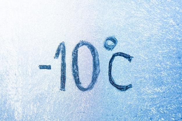 Cyfra 14 stopni fahrenheita lub -10 stopni celsjusza na lodowatym szkle pokrytym lodem i szronem. pojęcie ekstremalnych mrozów.