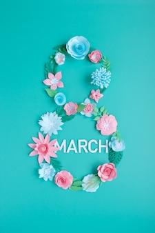 Cyfra 8 to kwiaty wycięte z różowo-niebieskiego papieru na neomiętowym tle.