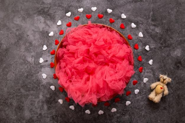 Cyfrowa fotografia noworodka na walentynki, czerwone i białe serca i miska