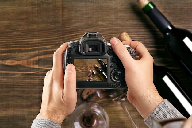 Cyfrowa lustrzanka jednoobiektywowa w rękach mężczyzny fotograf robi zdjęcia męskie ręce trzymają aparat c...