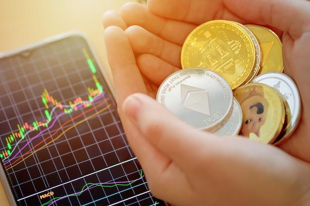 Cyfrowa moneta walutowa w kobiecej dłoni z telefonem pokazującym wykres giełdowy