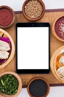 Cyfrowa tabletka otoczona parowcami; wiosenna cebula; nasiona sezamu i nasiona kolendry na podkładce