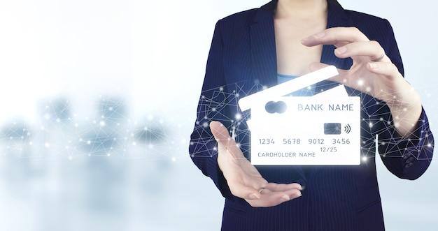 Cyfrowe płatności online i zakupy w połączeniu z siecią. dwie ręce trzymając wirtualną holograficzną ikonę karty kredytowej z jasnym tłem niewyraźne. koncepcje zakupów online lub sklepu internetowego.
