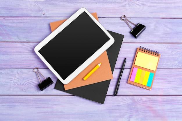 Cyfrowego pastylki i notepad biuro na purpurowy drewnianym