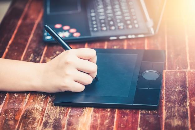 Cyfrowy artysta używający pisaka do pracy z komputerem przenośnym