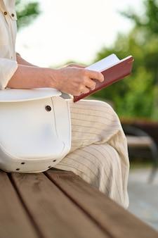 Cyfrowy detoks. kobieta w lekkich spodniach czytająca notatki siedząca na ławce w parku w pogodny dzień, bez twarzy