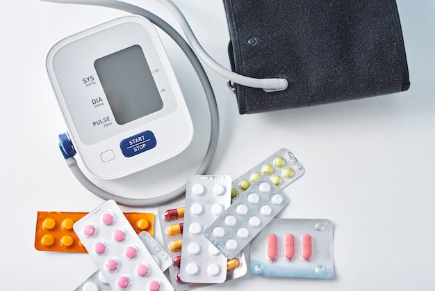 Cyfrowy monitor ciśnienia krwi i medyczne pigułki na bielu stole. pojęcie opieki zdrowotnej i medycyny