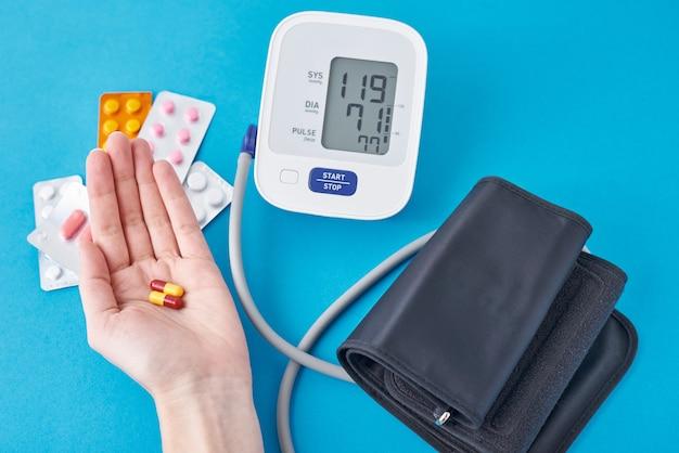 Cyfrowy monitor ciśnienia krwi i pigułki medyczne w ręku na niebiesko. pojęcie opieki zdrowotnej i medycyny