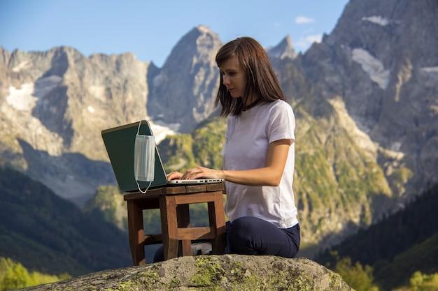 Cyfrowy nomad. kobieta pracuje na swoim laptopie przed górami. maska wisi na komputerze. niezależna koncepcja pracy zdalnej