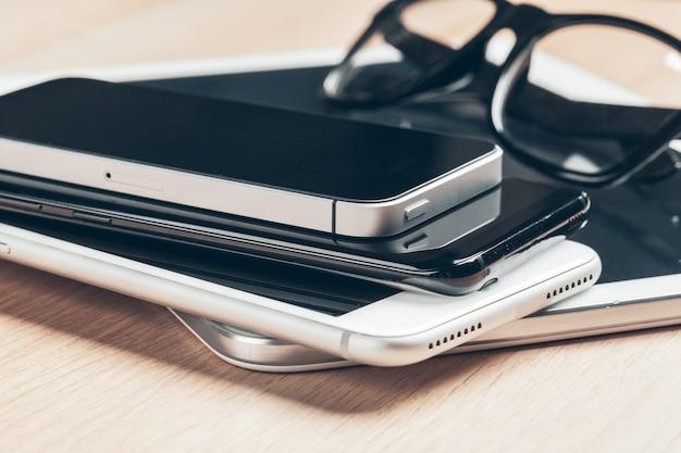 Cyfrowy tablet i telefon komórkowy. urządzenia elektroniczne na drewnianym stole, zamykają up.