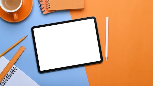 Cyfrowy tablet na tle dwóch tonów z materiałów biurowych.