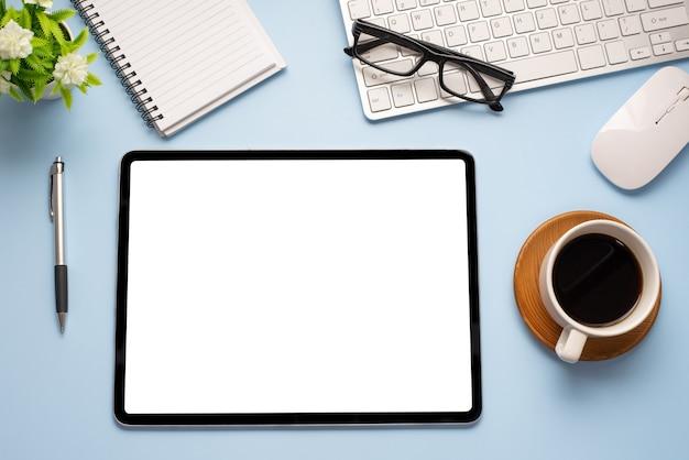 Cyfrowy tablet pusty biały ekran jest umieszczony na drewnianym stole w kolorze niebieskim w biurze.