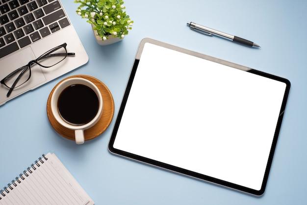 Cyfrowy tablet pusty biały ekran jest umieszczony na niebieskim drewnianym stole w biurze.