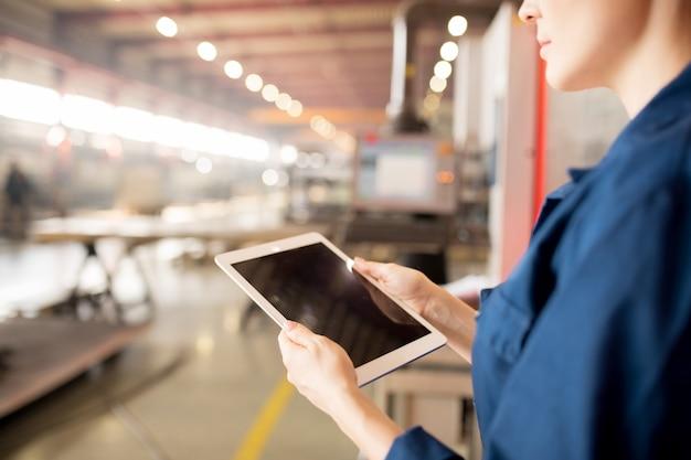 Cyfrowy tablet w rękach młodego, profesjonalnego technika surfującego po sieci w poszukiwaniu danych online obsługujących maszyny przemysłowe