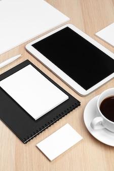 Cyfrowy tablet z notatnikiem, zapasami i filiżanką kawy na pulpicie.