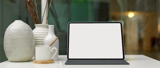 Cyfrowy tablet z pustym ekranem na nowoczesnym biurku w domu z filiżanką i ceramicznymi dekoracjami