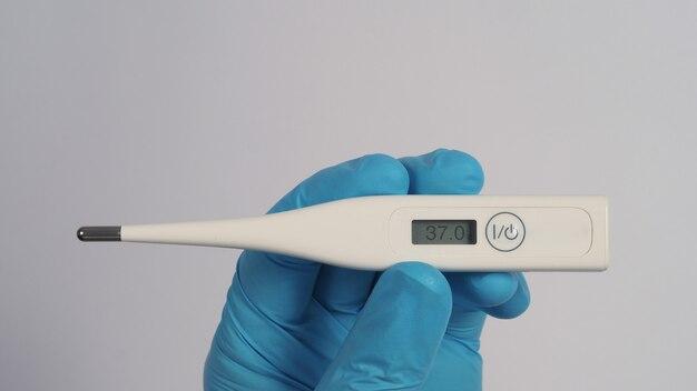 Cyfrowy termometr biały kolor w rękach lekarza w szpitalnych rękawiczkach medycznych jasnoniebieski kolor