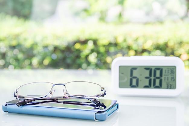 Cyfrowy zegar i okulary z filiżanką kawy