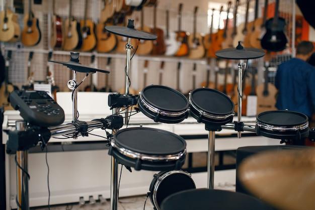Cyfrowy zestaw perkusyjny na gablocie w sklepie muzycznym, widok zbliżenie, nikt. asortyment w sklepie z instrumentami muzycznymi, profesjonalny sprzęt dla muzyków i wykonawców