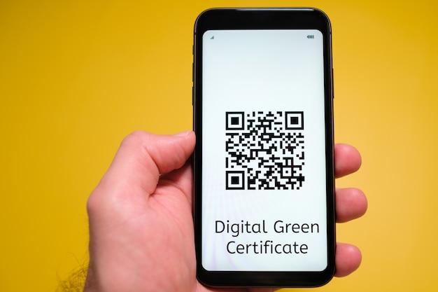 Cyfrowy zielony certyfikat z kodem qr na ekranie telefonu komórkowego w dłoni człowieka na żółto