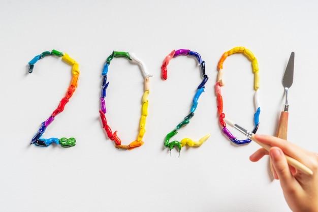 Cyfry 2020 są malowane na białym płótnie z jasnymi farbami olejnymi. widok z góry z bliska.