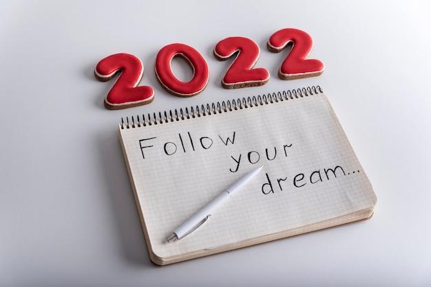 Cyfry 2022 i notes z napisem: follow your dream. lista życzeń na rok 2022.