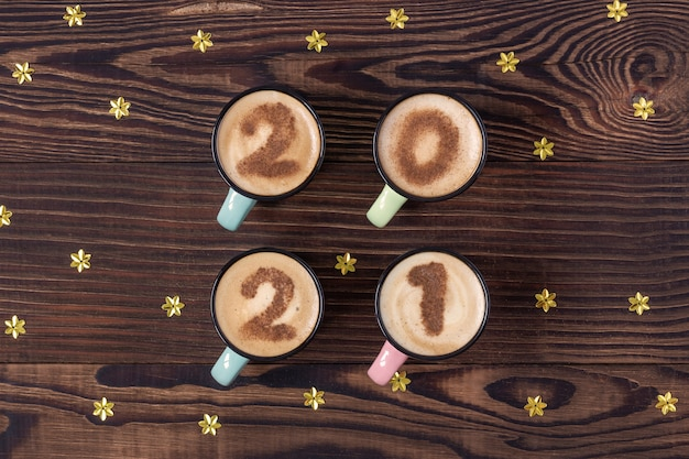 Cyfry w cztery kubki latte na podłoże drewniane
