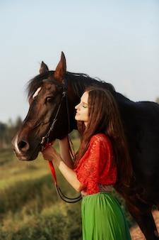 Cyganka jeździ konno w polu latem. kobieta z długimi włosami głaszcze i pieści konia stojącego w zielonej trawie