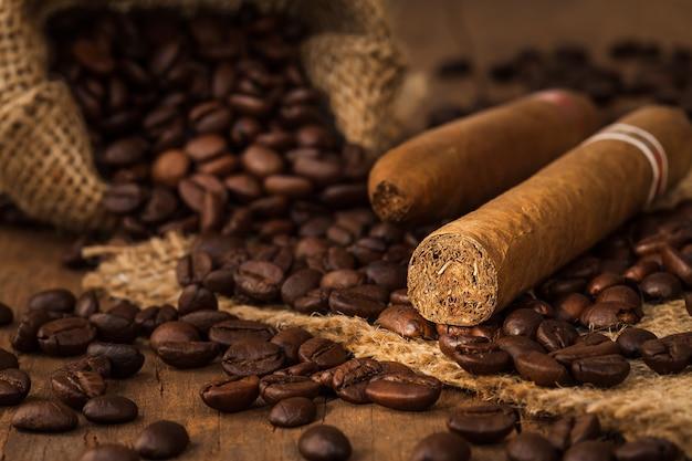 Cygara i ziarna kawy w małym worku na drewnianym stole