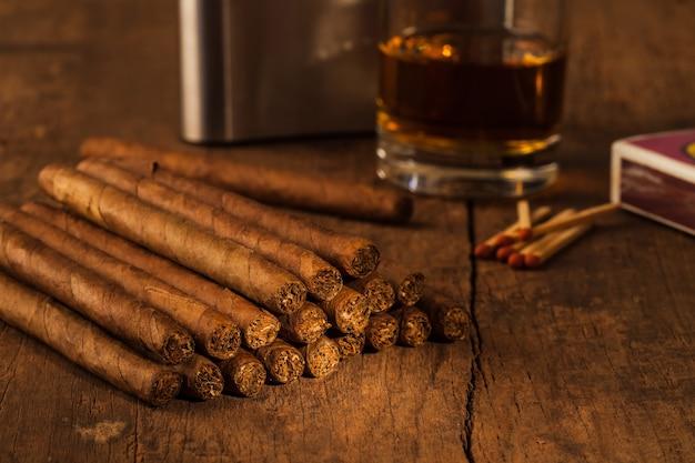 Cygaro na starym drewnianym stole z najlepszą whisky