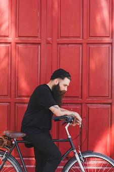 Cyklista jest ubranym kapeluszową pozycję z cyklem przed czerwonym drzwi