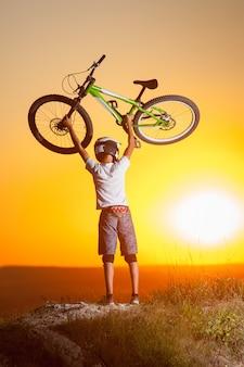 Cyklista z rowerem górskim na wzgórzu w wieczór