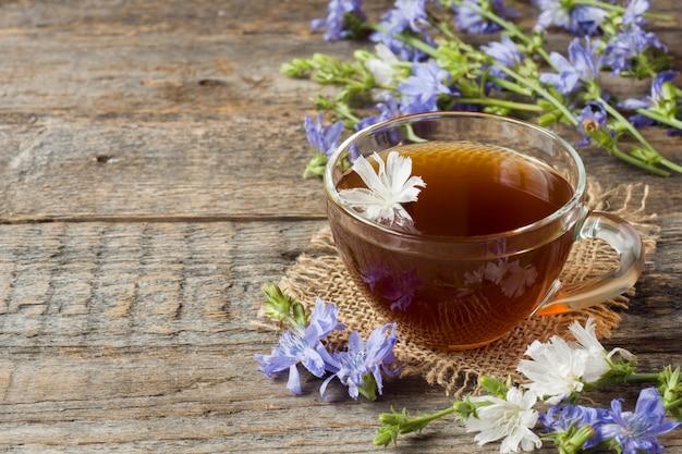 Cykoria napój w filiżance i kwiaty na nieociosanym drewnianym tle. roślina lecznicza cichorii.