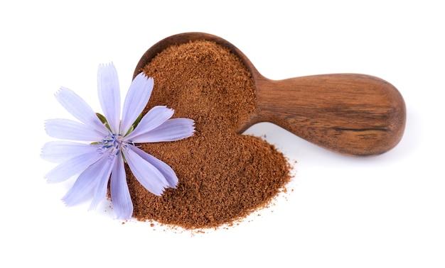Cykoria w proszku i kwiat w drewnianą łyżką, na białym tle. cichorium intybus.