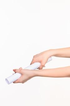 Cylinder w kobiecych rękach na białej ścianie