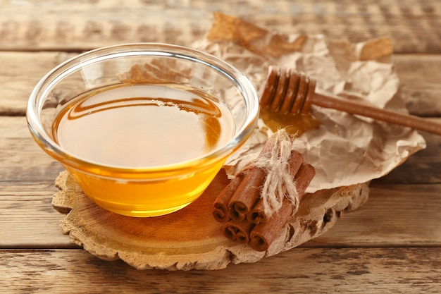 Cynamon i miód w misce na drewnianych