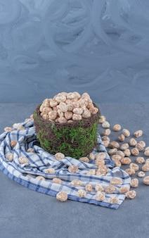 Cynamonowe cukierki w misce, na ręczniku na marmurowym tle.