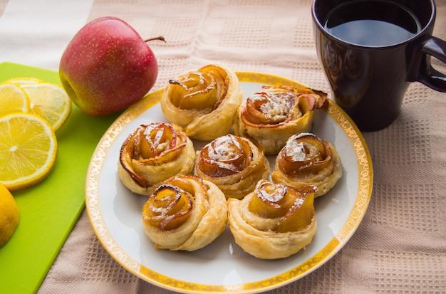 Cynamonowe rolki, apple na talerzu. filiżanka herbaty i cytryna
