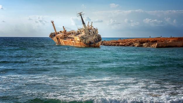 Cypr, pafos. wrak statku. statek rozbił się o skały przybrzeżne. zardzewiały statek na brzegu morza śródziemnego. atrakcje turystyczne cypru.