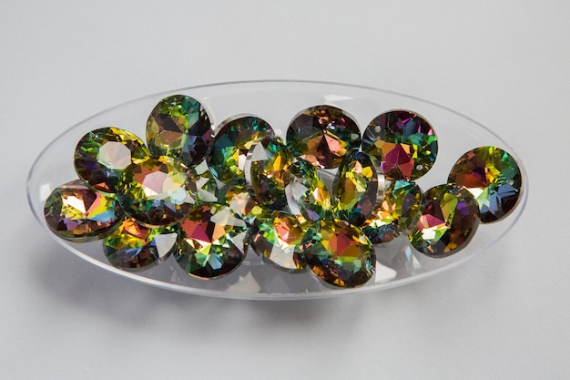 Cyrkonie z płaskiego grzbietu i wielokolorowych kamieni leżące w przezroczystej plastikowej misce